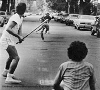 Boys playing stickball in street