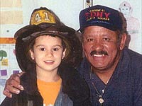 Sammy Marquez with grandson proudly wearing his firefighter gear